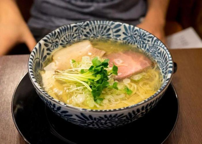 White and blue patterned ramen in bowl with light broth, green garnish, and meat inside, with person's hands in background