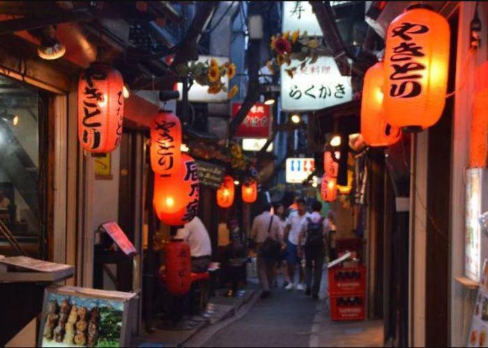 Dark street alley with hanging red lanterns saying izakaya hanging in restaurant doorways