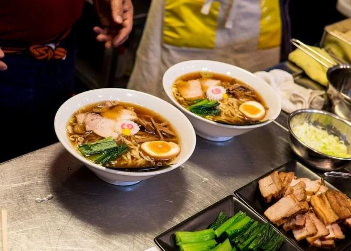 Two white bowls of dark broth ramen topped with naruto, egg, greens, meat; dishes of toppings on counter