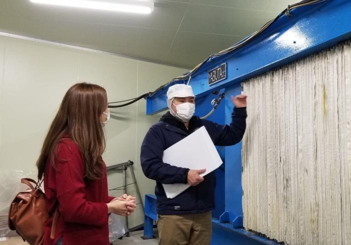 Sugawara Hiroki gives a tour to Shizuka Anderson at Otokoyama Honten Sake Brewery, showing her the sake pressing machine