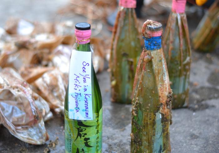 """Underwater aged sake bottles with a label reading """"See you in Kesennuma"""""""