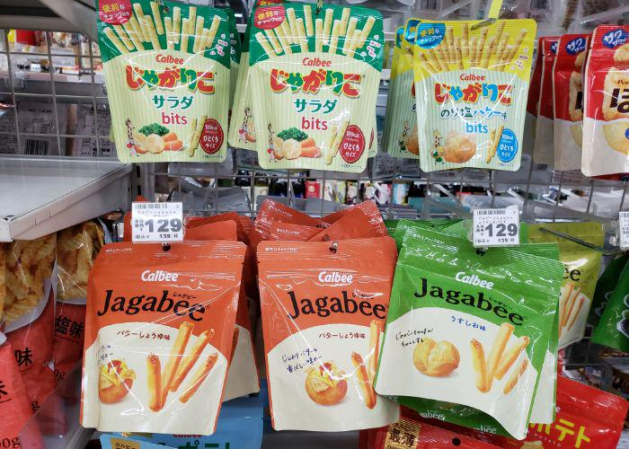 Six small bags of potato stick snacks hanging on convenience store shelves