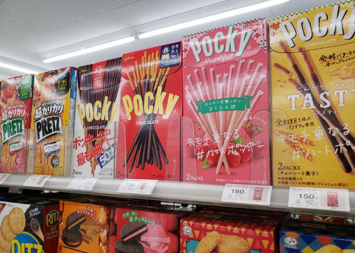 Colorful boxes of different flavors of Pocky lined up on convenience store shelf