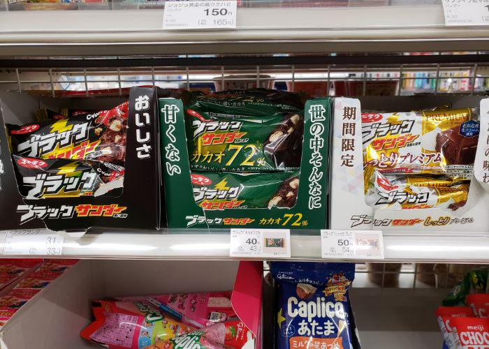 Three small boxes of different varieties of Black Thunder chocolate candy bars on convenience store shelf