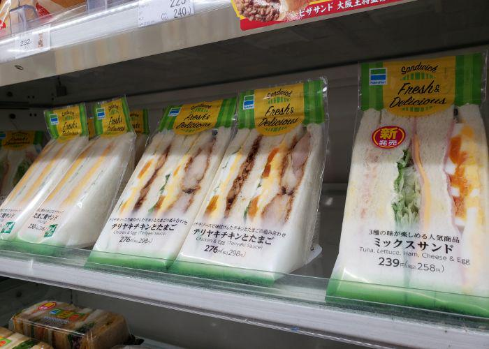 Several clear packages of two sandwiches of different varieties cut in triangles with fillings visible on convenience store shelf