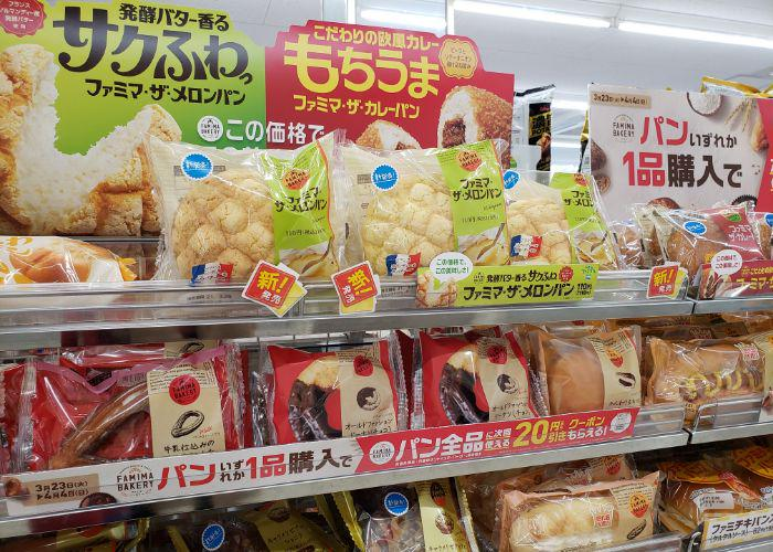 Family Mart shelves filled with different limited time breads, large signs advertising melon pan, curry pan