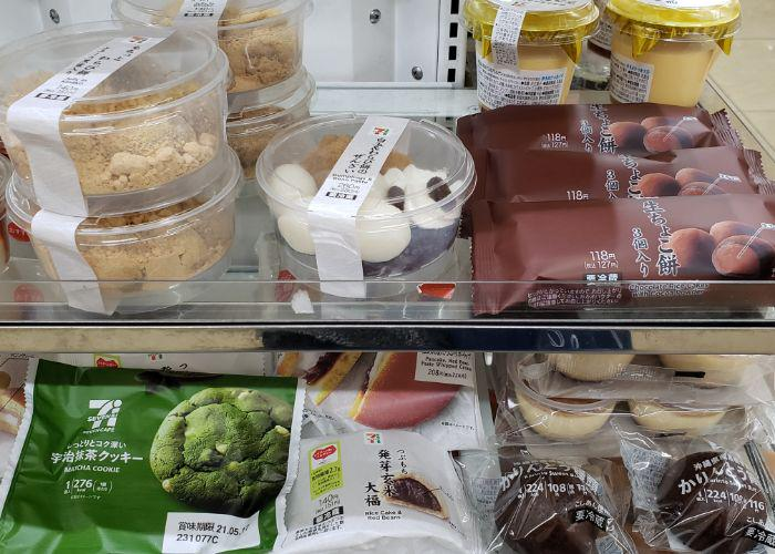 7-eleven refrigerated shelf with traditional Japanese sweets like chocolate mochi, a matcha cookie, red bean rice cake