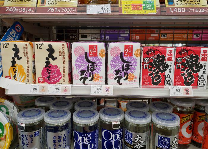 Six rows of wine and sake in small square juice boxes on convenience store shelves, two with Japanese demons on them
