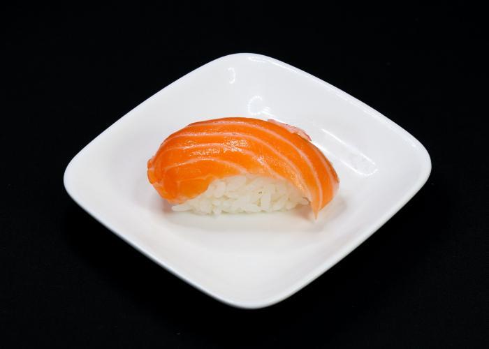 Atlantic Salmon nigiri sushi on a white plate with a black background