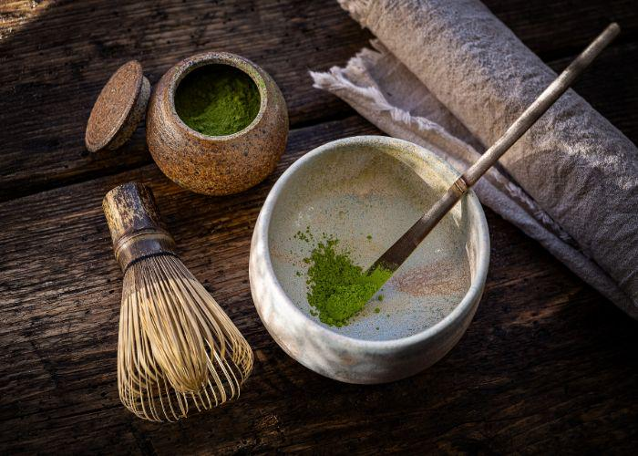 An overhead image of powdered matcha tea in a bowl, with a chasen whisk beside it
