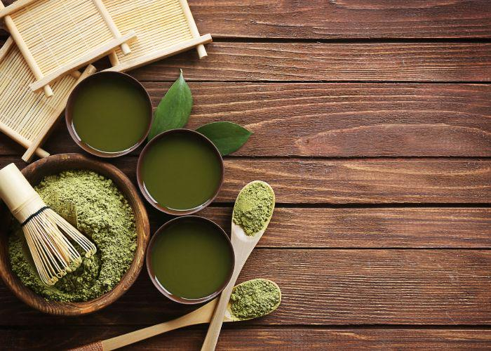 An overhead image of a bowl of green matcha powder with a whisk on top, and three cups of matcha tea