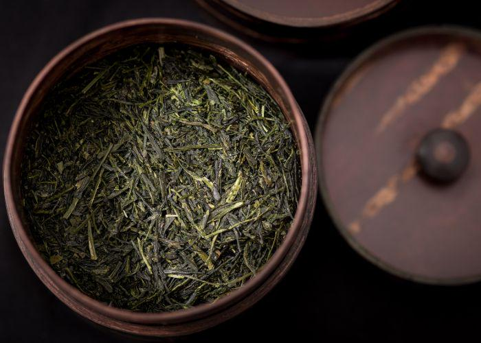 A close up image of a wooden pot full of dried, dark green gyokuro tea leaves