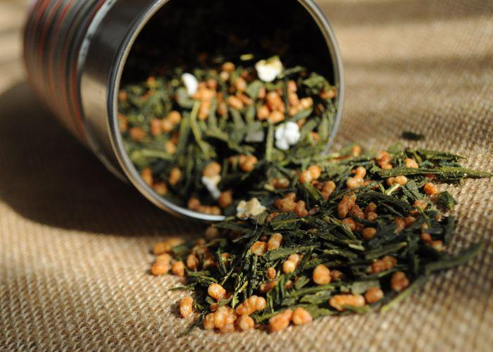 A close up image of a tin of genmaicha tea spilling out onto cloth, with dried tea leaves and roasted rice