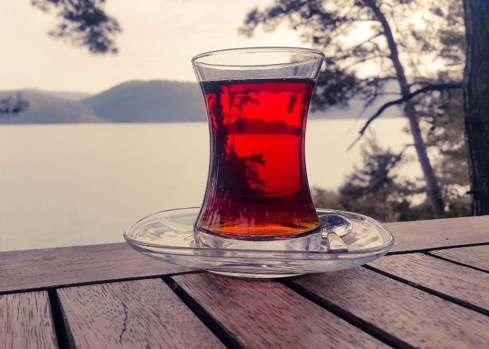 A glass of kocha tea on a wooden table, with a body of water and mountains in the background
