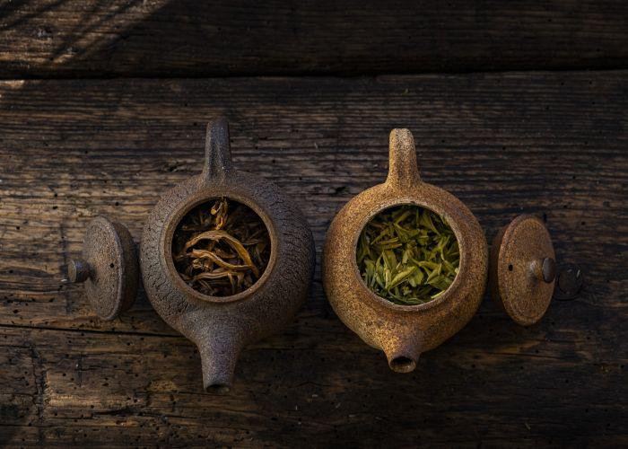 An overhead shot of two traditional teapots filled with tea leaves