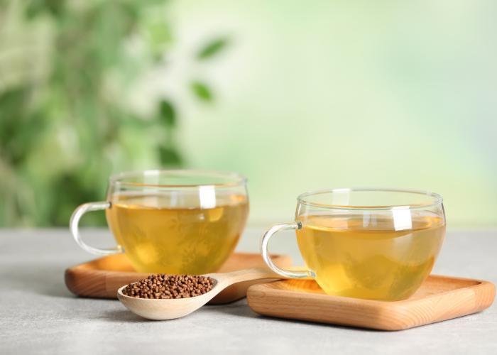 Sobacha buckwheat tea in clear teacups with a small dish of buckwheat