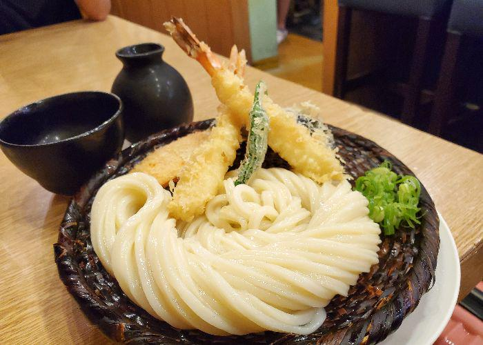 Bowl of udon noodles accompanied by tempura at Udon from Shin Udon