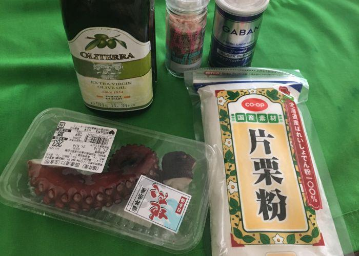 Tako karaage ingredients including boiled octopus tentacles and potato starch, laid on on a green tablecloth