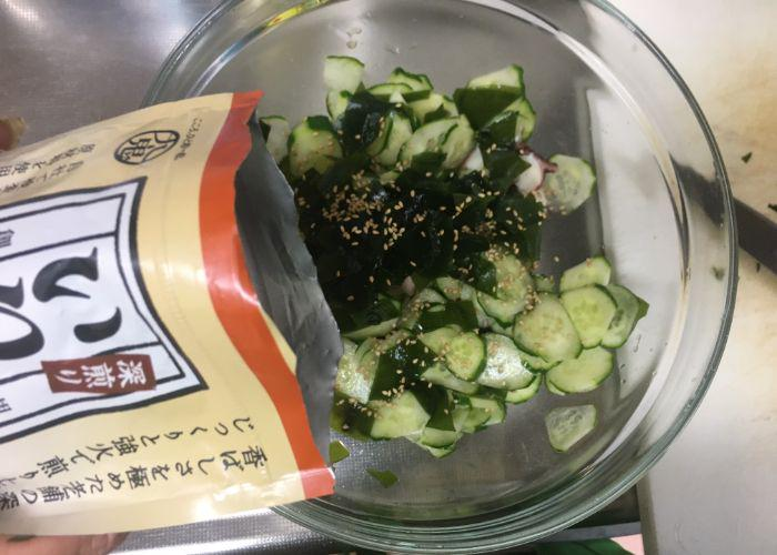 Hand adding sesame seeds to a bowl of takosu ingredients