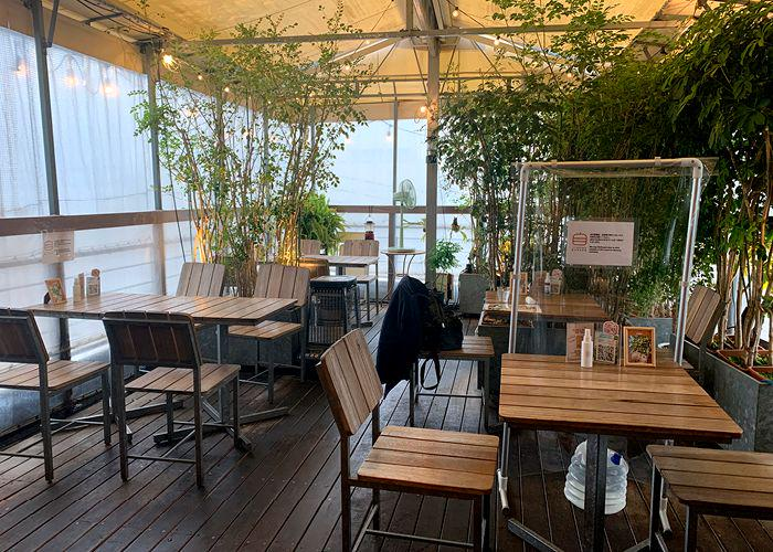 Jiyugaoka Burger interior with wooden tables and chairs and tall plants