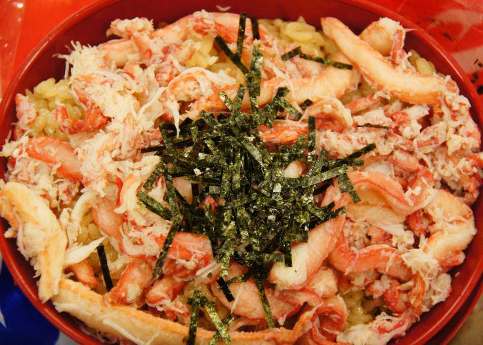 A close up image of crab meat mixed with rice and topped with dried seaweed