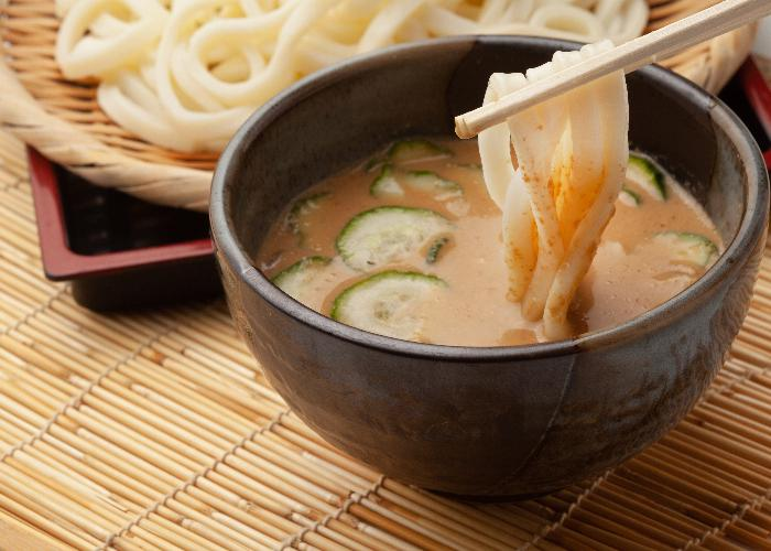 Hiyajiru udon, a dipping sauce with cold cucumbers and a plate of udon noodles in the background