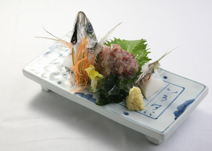 Namerou, minced fish plated on a dish with wasabi, shiso, and a fish head