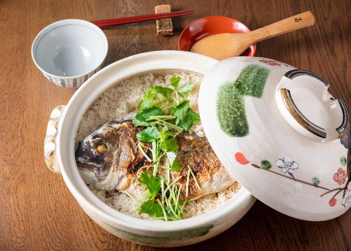 A small nabe pot filled with rice and topped with a sea bream