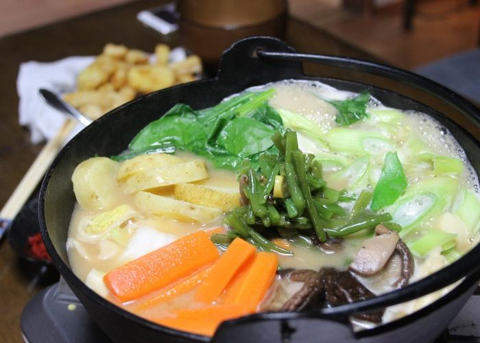 Hoto noodles cooking in an iron pot with carrots and other veggies