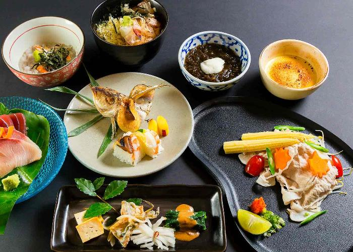Colorful Japanese kaiseki ryori dishes laid out on a gray table