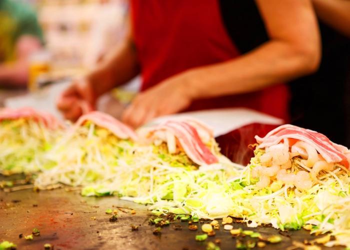 Hiroshima okonomiyaki being made on a teppan griddle