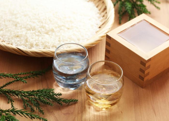 Two glasses of Japanese sake next to a wooden tray of rice