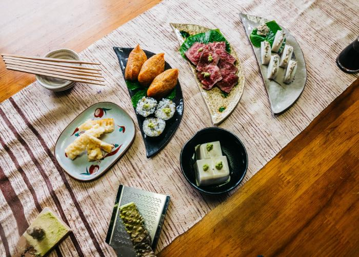 An overhead shot of several dishes paired with Japanese wasabi: sushi rolls, tempura, fish cakes, and more