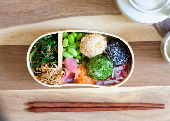 Colorful vegetable bento box filled with rice balls and veggies