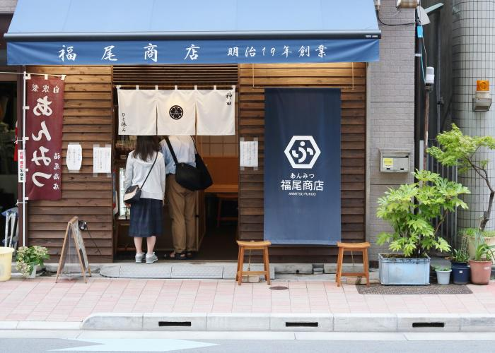 Two people stand under the noren of a Japanese anmitsu shop