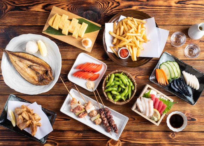 A spread of izakaya appetizers including tamagoyaki, chicken wings, grilled fish, kamaboko, sashimi and more