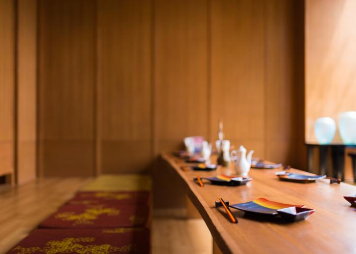 Japanese restaurant interior with cushioned floor seating and a table set with chopsticks and plates