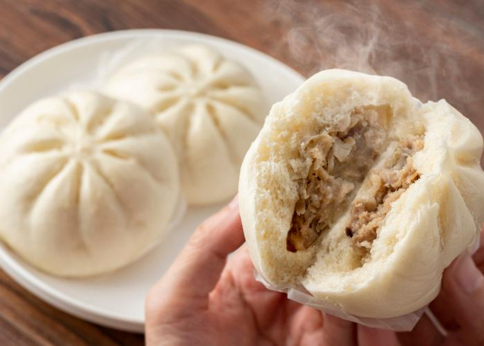 Japanese nikuman, a plate of steamed buns and close up of hands breaking a steamed bun in half