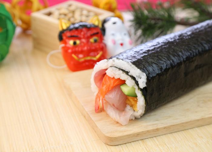 Ehomaki, a thick Japanese sushi roll on a cutting board in front of demon masks
