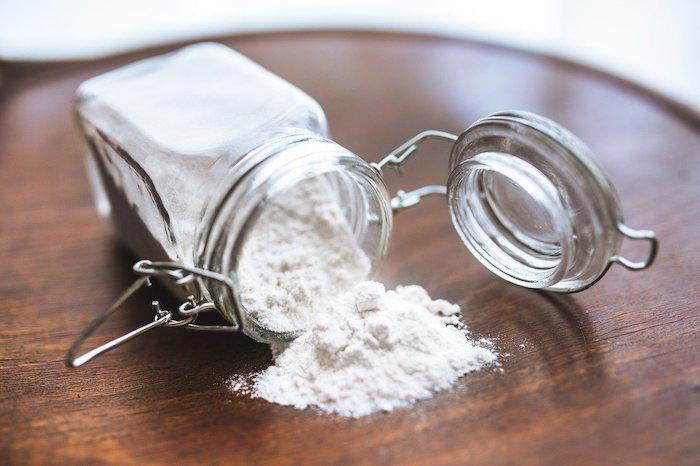 Potato Starch in a Jar spilling onto wooden table