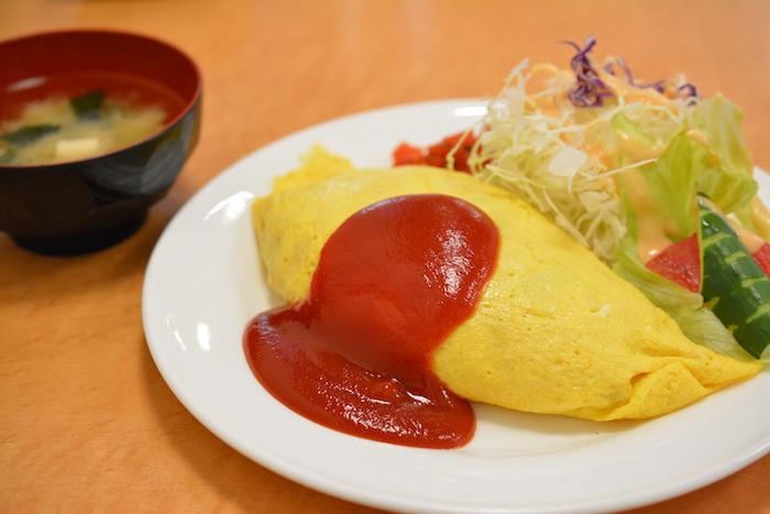 Omurice on a plate with salad next to a bowl of miso soup