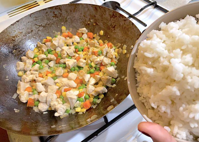 Adding the rice into the wok with vegetables for omurice