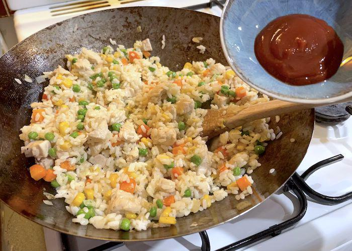 Adding Ketchup to wok with rice mix for Omurice