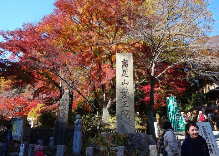 The stone sign at the summit of Mt Takao, surrounded by fall foliage