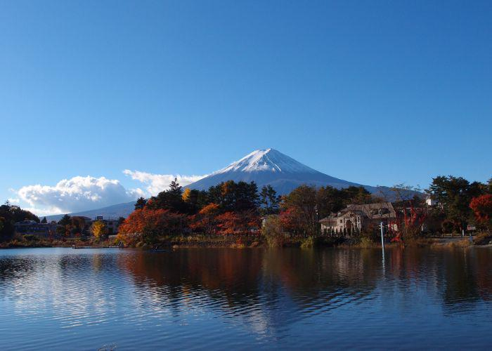 A photo of Mount Fuji from across Lake Kawaguchi, with red and orange trees in front