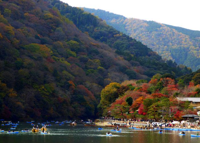 People riding boats on the river in Arashiyama with the forested mountains behind covered in red and orange trees