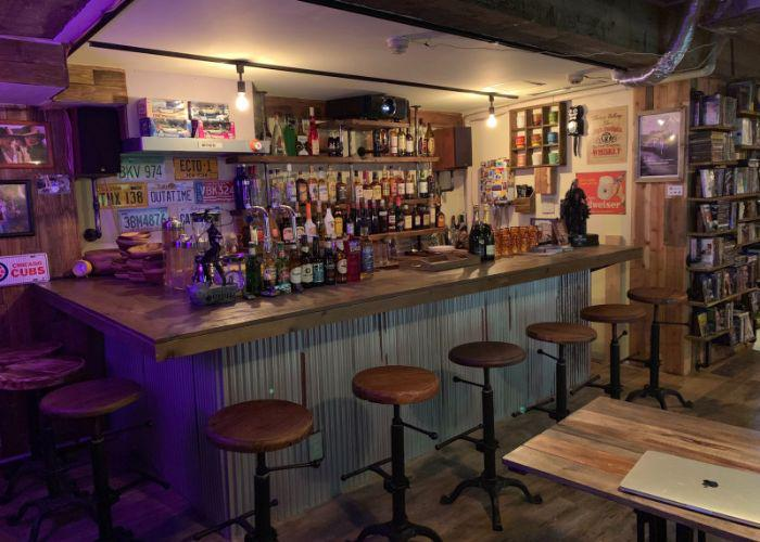 American-style bar with wooden barstools and a large selection of alcohol