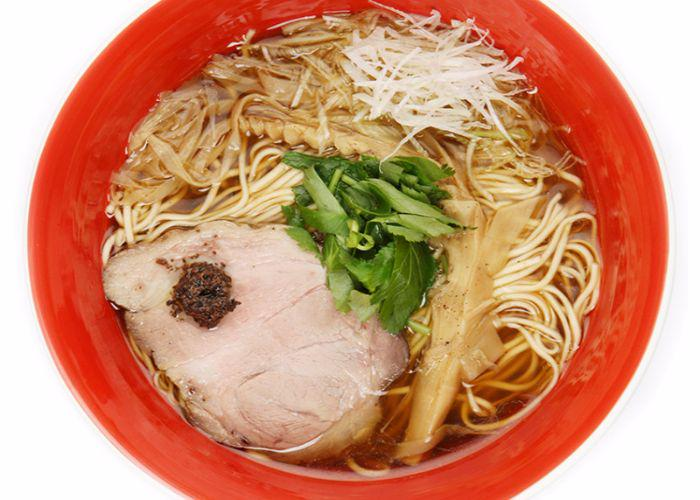 Shoyu Ramen at Tsuta, a Michelin-starred ramen restaurant in Tokyo. Red bowl with a thick slice of chashu pork and straight ramen noodles.
