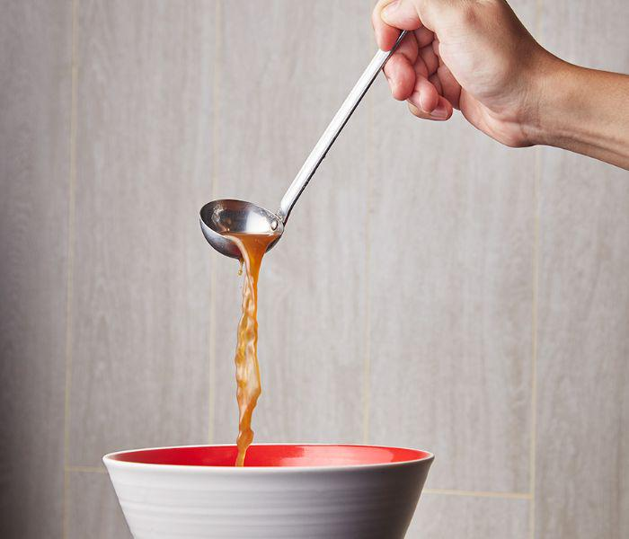Hand holding a ladle full of hot soup broth, pouring soup into a ramen bowl