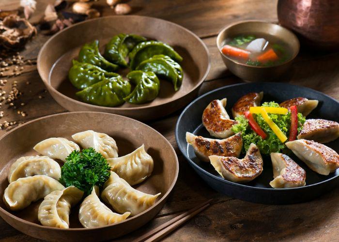 3 plates of gyoza, Japanese dumplings: pan-fried gyoza, steamed gyoza with broccoli, and green gyoza,